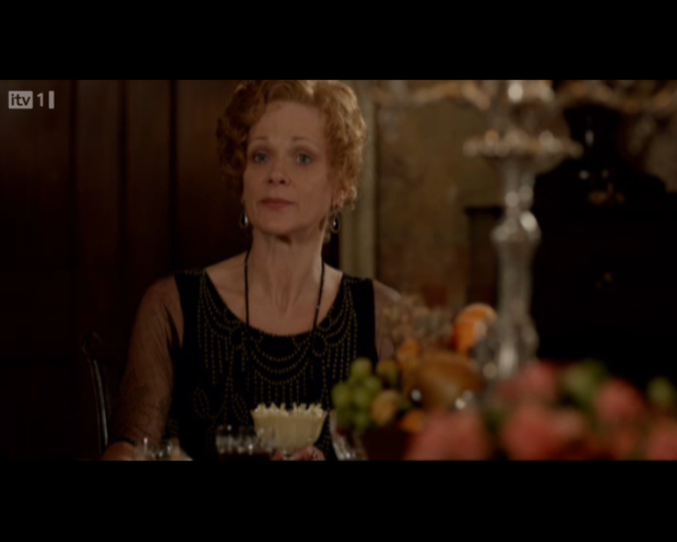Lady Rosamund in a wonderful black evening dress, complimented by a long strand of black beads.