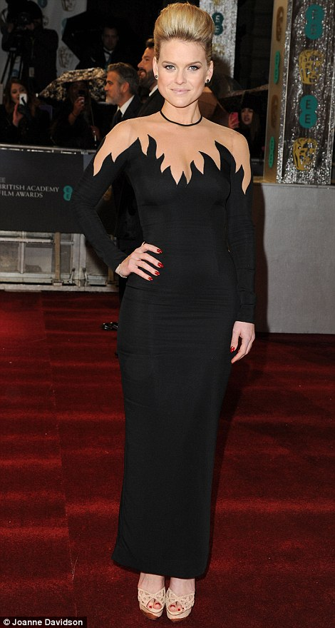 Alice Eve sets the Little Black Dress on fire with this daring dress. Her up-do hair lets the dress speak for itself, and her bright red nails suggest that this girl is on fire. Looking fierce!